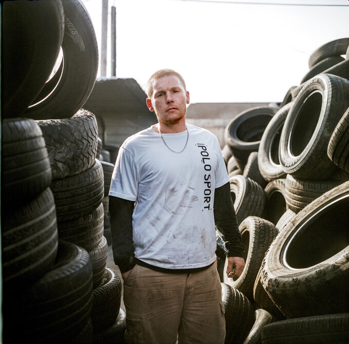 "In this photo made with a medium format film camera, Steven Ash, 33, stands for a portrait while working at the tire shop his family owns and where he overdosed just days before in Huntington, W.Va., Wednesday, March 17, 2021. Ash was 19 when he took his first OxyContin pill and his life unraveled after that, cycling through jails, he said. The last year has been particularly brutal. His cousin died from an overdose in somebody's backyard. He has a friend in the hospital in her 20s scheduled for open-heart surgery from shooting drugs with dirty needles, and the doctors aren't sure she'll make it. He had three agonizing surgeries himself from drug-related infections. He took more drugs to numb the pain, but it made things worse, a vicious cycle, he said. He knows he's putting his mother through hell. ""I fight with myself every day. It's like I've got two devils on one shoulder and an angel on the other,"" he said. ""Who is going to win today?"" (AP Photo/David Goldman)"