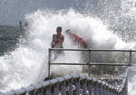 Residents cling to the railing as a wave generated by Hurricane Dorian crashes into the jetty at Lighthouse Point Park in Ponce Inlet, Fla., Monday, Sept. 2, 2019. (Joe Burbank/Orlando Sentinel via AP)
