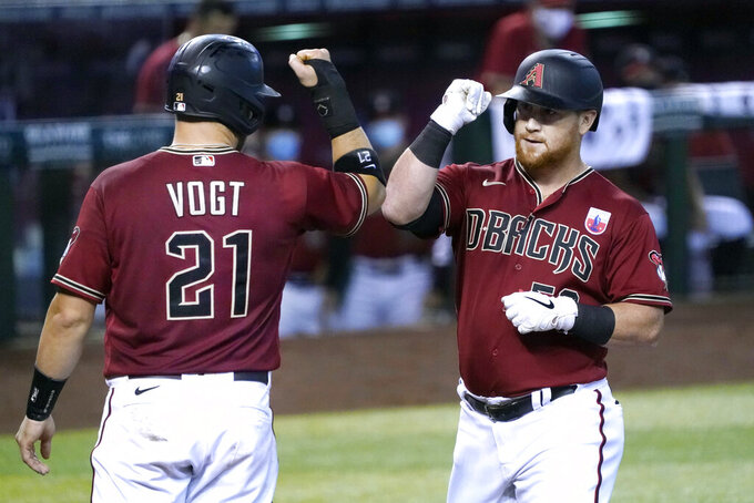 Arizona Diamondbacks' Kole Calhoun celebrates with Stephen Vogt (21) after hitting a two-run home run against the San Diego Padres in the third inning during a baseball game, Sunday, Aug 16, 2020, in Phoenix. (AP Photo/Rick Scuteri)