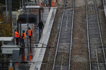 Informations workers stand on a platform at an empty Paris suburb train station Thursday, Dec. 12, 2019 in Sevres, west of Paris. Unions have flatly rejected fresh proposals by the government of pro-business President Emmanuel Macron to stagger the roll-out of a plan that would require France's youngest workers - people born after 1974 - to stay on the job until the age of 64 to get full pensions instead of age 62. (AP Photo/Christophe Ena)