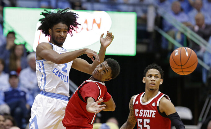 North Carolina's Coby White, left, passes while North Carolina State's Markell Johnson, center, and Blake Harris, right, defend during the second half of an NCAA college basketball game in Chapel Hill, N.C., Tuesday, Feb. 5, 2019. North Carolina won 113-96. (AP Photo/Gerry Broome)