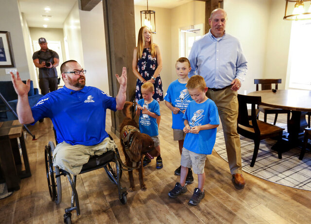 Purple Heart veteran U.S. Army Sgt. 1st Class Travis Vendela, left, his wife, Tiffany, center, their three sons, Kaiden, Quentin and Trayden, and Andrew McClure, Tunnel to Towers national community engagement coordinator, tour the Vendelas' new home in Huntsville, Weber County, on Friday, July 3, 2020. (Laura Seitz/The Deseret News via AP)