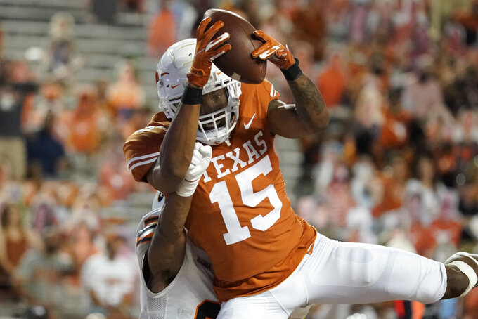 Texas's Marcus Washington (15) catches a touchdown pass against UTEP during the second half of an NCAA college football game in Austin, Texas, Saturday, Sept. 12, 2020. (AP Photo/Chuck Burton)