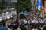 Commuters fill the street during the evening rush hours in the Shinjuku district of Tokyo, June 12, 2019. (AP Photo/Jae C. Hong)