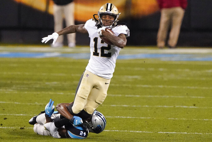 New Orleans Saints wide receiver Marquez Callaway is tackled by Carolina Panthers cornerback Rasul Douglas during the first half of an NFL football game Sunday, Jan. 3, 2021, in Charlotte, N.C. (AP Photo/Brian Blanco)