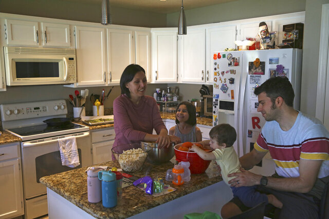 Katherine Rutigliano prepares a meal with her husband, Elio, right, along with their son, Theo, and daughter, Charlotte, at their home in Phoenix, Ariz., on March 16, 2020. When the couple moved away from San Francisco in 2013, they figured they would never meet a fellow Democrat again. Rutgliano didn't realize it, but she had moved her family to what is now the front lines in American politics. (AP Photo/Dario Lopez-Mills)