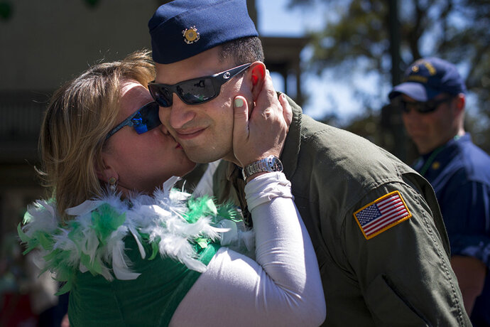 FILE - In a Friday, March 17, 2017 file photo, a woman kisses a member of the U.S. Coast Guard during Saint Patrick's Day Parade in Savannah, Ga. The Army wants to halt the favorite St. Patrick's Day shenanigan in Savannah that for decades has left marching soldiers with lipstick-smeared cheeks. Roughly 200 soldiers from nearby Fort Stewart are expected to march in the coastal Georgia city's sprawling St. Patrick's Day parade March 17, 2018. Traditionally, women wearing bright lipstick dart from the crowd to plant kisses on the faces of passing troops. A Fort Stewart spokesman and the parade's chief organizer said Thursday the Army wants the soldier smooching stopped. (Josh Galemore/Savannah Morning News via AP, File)