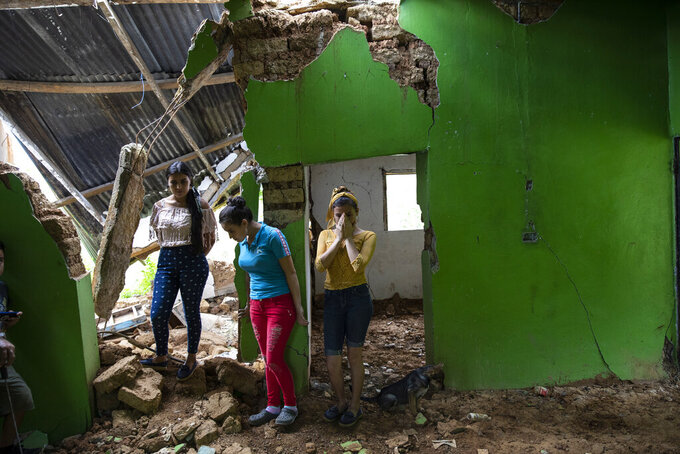 Marian Castron, from left, Maria Castron, 25, and Jenny Castron, 19, visit their home devastated by a landslide triggered by consecutive hurricanes in La Reina, Honduras, Friday, June 25, 2021. The Honduran town was hammered in November 2020 by Hurricanes Eta and Iota and then obliterated by a mudslide. (AP Photo/Rodrigo Abd)