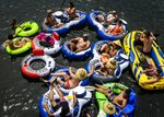 FILE - In this May 24, 2020, file photo, a group of at least 15 people float on connected inflatables down the American River in the Sunrise Recreation Area near Rancho Cordova, Calif., during Memorial Day weekend. California's mood has gone from optimistic to sour as coronavirus cases and hospitalizations are on the rise heading into the July 4th weekend. Gov. Gavin Newsom has ordered bars and indoor restaurant dining closed in most of the state, many beaches are off limits, and he's imploring Californians to avoid holiday gatherings with family and friends. (Daniel Kim/The Sacramento Bee via AP, File)
