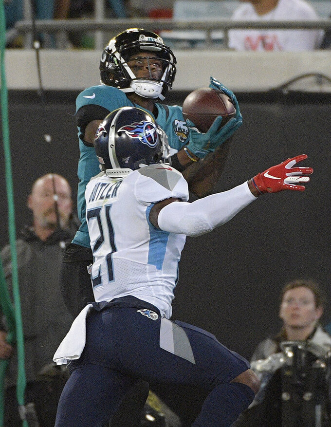 Jacksonville Jaguars wide receiver D.J. Chark (17) pulls in a 22-yard touchdown pass in front of Tennessee Titans cornerback Malcolm Butler (21) during the first half of an NFL football game Thursday, Sept. 19, 2019, in Jacksonville, Fla. (AP Photo/Phelan Ebenhack)
