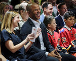 FILE - In this July 30, 2018, file photo, former Calgary Flames captain Jarome Iginla, center, laughs as his wife Kara, left, applauds during his retirement ceremony from the NHL, after playing 20 seasons, at a news conference in Calgary, Alberta. Iginla, the first Black player to lead the NHL in points and goals and to win an Olympic gold medal, is expected to headline the Hockey Hall of Fame's 2020 induction class, to be announced Wednesday, June 24, 2020. (Jeff McIntosh/The Canadian Press via AP, File)