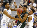 Michigan State forward Xavier Tillman (23) looks to pass the ball as he is covered by Duke center Marques Bolden (20) guard Tre Jones (3) during the first half of an NCAA men's East Regional final college basketball game in Washington, Sunday, March 31, 2019. (AP Photo/Patrick Semansky)