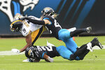 Pittsburgh Steelers wide receiver JuJu Smith-Schuster (19) is bright down after a reception by Jacksonville Jaguars cornerback Chris Claybrooks, bottom and safety Andrew Wingard (42) during the second half of an NFL football game, Sunday, Nov. 22, 2020, in Jacksonville, Fla. (AP Photo/Matt Stamey)