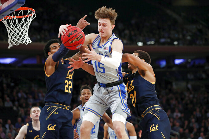 Duke guard Alex O'Connell (15) grabs the ball in front of California forward Andre Kelly (22) and California guard Matt Bradley (20) during the first half of the first round of the 2K Empire Classic NCAA college basketball tournament, Thursday, Nov. 21, 2019, in New York. (AP Photo/Kathy Willens)