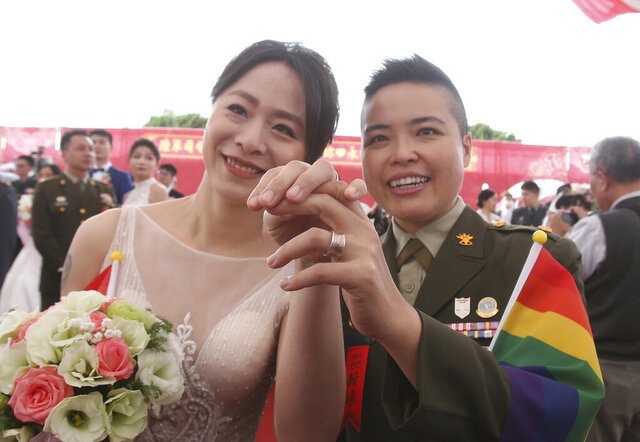 Lesbian couple Yi Wang, right, and Yumi Meng show their wedding rings during a military mass weddings ceremony in Taoyuan city, northern Taiwan, Friday, Oct. 30, 2020. Two lesbian couples tied the knot in a mass ceremony held by Taiwan's military on Friday in a historic step for the island. Taiwan is the only place in Asia to have legalized gay marriage, passing legislation in this regard in May 2019. (AP Photo/Chiang Ying-ying)