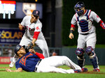 Minnesota Twins' Jonathan Schoop, bottom left, is tagged out by Boston Red Sox third baseman Rafael Devers, top left, while Red Sox catcher Sandy Leon looks on in the eighth inning of a baseball game Monday, June 17, 2019, in Minneapolis. (AP Photo/Andy Clayton- King)