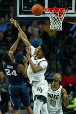Xavier guard KyKy Tandy, left, shoots against Wake Forest forward Ody Oguama as Wake Forest guard Andrien White (13) looks on in the first half of an NCAA college basketball game in Winston-Salem, N.C., Saturday, Dec. 14, 2019. (AP Photo/Nell Redmond)
