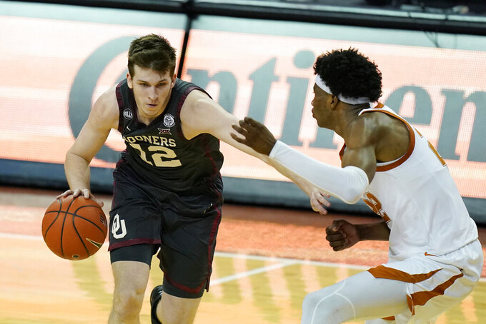 Oklahoma guard Austin Reaves (12) drives against Texas forward Kai Jones during the second half of an NCAA college basketball game Tuesday, Jan. 26, 2021, in Austin, Texas. (AP Photo/Eric Gay)