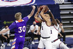 Gonzaga guard Jalen Suggs, center, grabs a rebound next to teammate guard Joel Ayayi, right, and Northwestern State guard Trenton Massner during the first half of an NCAA college basketball game in Spokane, Wash., Monday, Dec. 21, 2020. (AP Photo/Young Kwak)