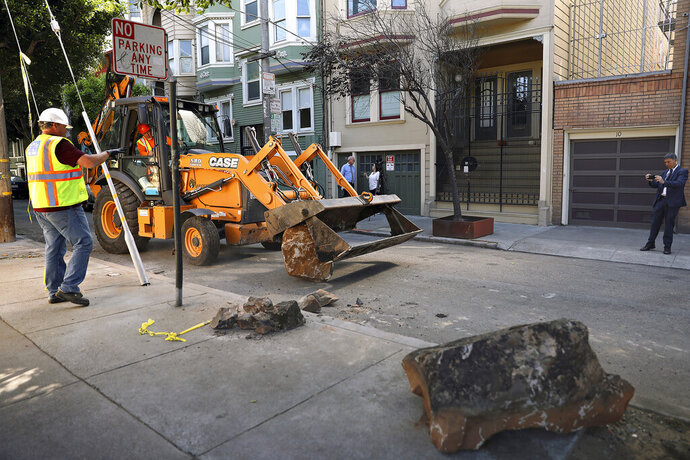In this Monday, Sept. 30, 2019, photo, a San Francisco Public Works crew removes boulders from a sidewalk along a street in San Francisco, Monday, Sept. 30, 2019. A group of San Francisco neighbors say they bought boulders and had them delivered to their sidewalk to stop people from camping and dealing drugs on their street. (Liz Hafalia/San Francisco Chronicle via AP)