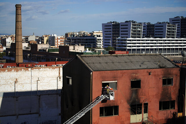 Firefighters load the body of a dead person into a crane after a fire on a building in Badalona, Barcelona, Spain, Thursday, Dec. 10, 2020. Authorities in northeastern Spain say a fire has raged through an abandoned building occupied by squatters in the city of Badalona, injuring at least 17 people, including two in critical condition. Firefighters say they rescued around 30 people from windows as the building burned late Wednesday. (AP Photo/Joan Mateu)