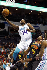 Charlotte Hornets' Michael Kidd-Gilchrist (14) gets his shot off as he drives by Atlanta Hawks' Vince Carter (15) during the first half of an NBA basketball game in Charlotte, N.C., Sunday, Dec. 8, 2019. (AP Photo/Bob Leverone)