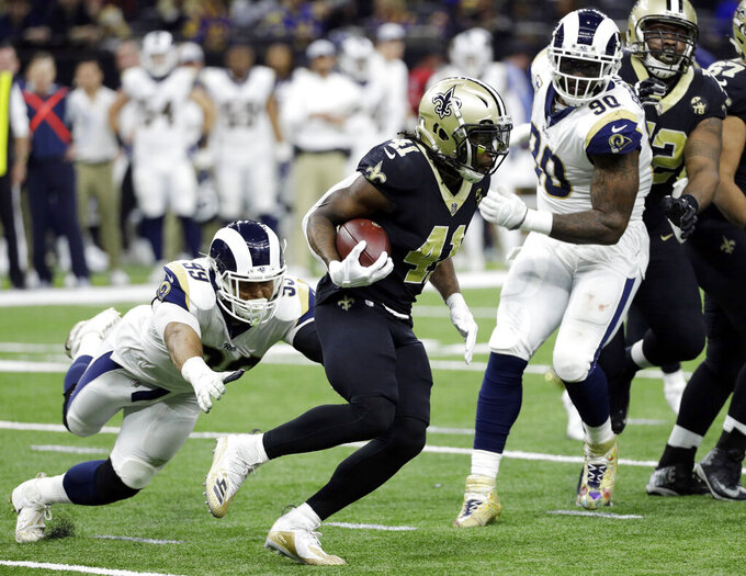New Orleans Saints' Alvin Kamara runs against Los Angeles Rams defensive end Aaron Donald (99) during the first half of the NFL football NFC championship game against the Los Angeles Rams, Sunday, Jan. 20, 2019, in New Orleans. (AP Photo/David J. Phillip)