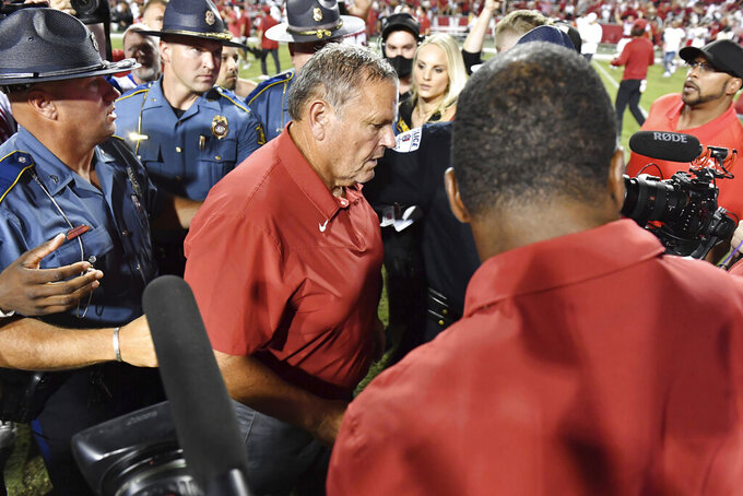Arkansas coach Sam Pittman is escorted off the field after the team's win over Texas in an NCAA college football game Saturday, Sept. 11, 2021, in Fayetteville, Ark. (AP Photo/Michael Woods)