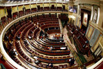 Spain's Prime Minister Pedro Sanchez, right, speaks in a nearly empty parliament while the majority of lawmakers follow the session online before a vote to approve the extension of the national lockdown in Madrid, Spain, Wednesday, March 25, 2020. Spain released new figures of the official number of deaths in Spain because of the COVID-19 coronavirus, surpassing China's death toll. The new coronavirus causes mild or moderate symptoms for most people, but for some, especially older adults and people with existing health problems, it can cause more severe illness or death. (Mariscal, Pool photo via AP)