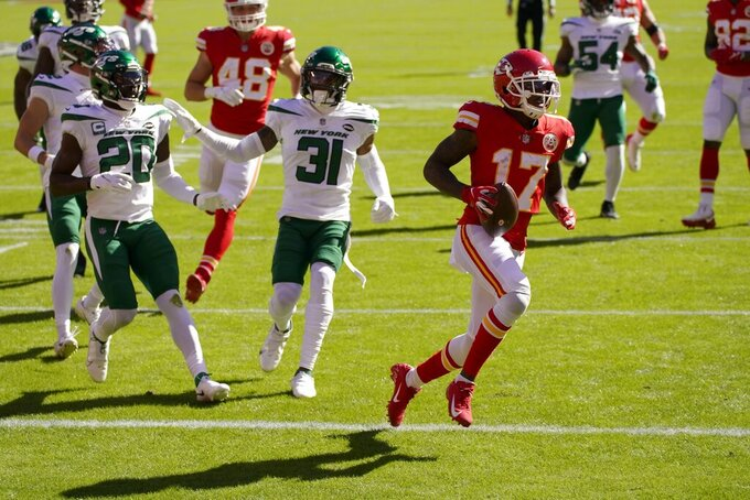 Kansas City Chiefs wide receiver Mecole Hardman (17) scores a touchdown after catching a pass as New York Jets' Marcus Maye (20) and Bless Austin (31) give chase in the first half of an NFL football game on Sunday, Nov. 1, 2020, in Kansas City, Mo. (AP Photo/Charlie Riedel)