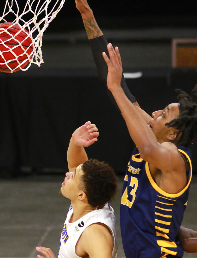 UC Irvine's Austin Johnson (13) dunks the ball over UC Santa Barbara's Jaquori McLaughlin (3) in the first half of an NCAA college basketball game for the championship of the Big West Conference men's tournament Saturday, March 13, 2021, in Las Vegas. UC Santa Barbara won 79 to 63. (AP Photo/Ronda Churchill)