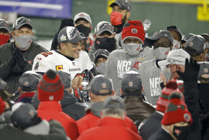 Tampa Bay Buccaneers quarterback Tom Brady (12) holds the championship trophy after winning the NFC championship NFL football game against the Green Bay Packers in Green Bay, Wis., Sunday, Jan. 24, 2021. The Buccaneers defeated the Packers 31-26 to advance to the Super Bowl. (AP Photo/Mike Roemer)