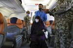 An Albanian woman, center, boards a plane, during an operation to take home five Albanians from al-Hol, northern Syria, in Beirut, Lebanon, Tuesday, Oct. 27, 2020. The repatriation of four children and a woman related to Albanian nationals who joined Islamic extremist groups in Syria