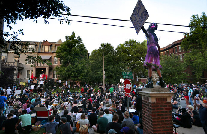 A protester's sign calls for the resignation of St. Louis Mayor Lyda Krewson during a rally in front of her home on Lake Avenue in St. Louis, on Sunday, June 28, 2020. The protesters demanded Krewson's resignation after she read the names and addresses of several residents who supported defunding the police department during an online briefing.   (Robert Cohen/St. Louis Post-Dispatch via AP)