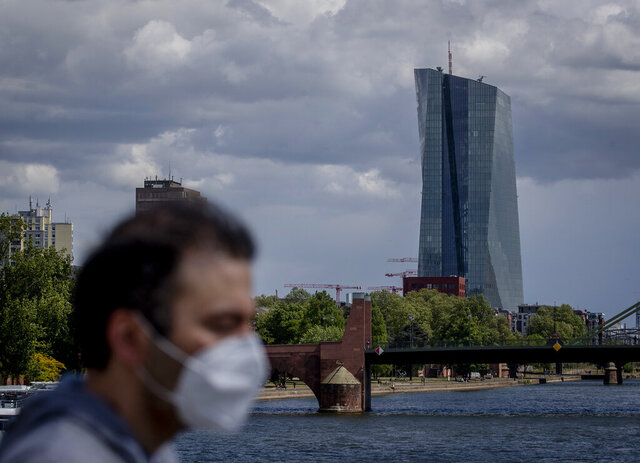 FILE - In this Wednesday, April 29, 2020 file photo, a man walks in front of the European Central Bank in Frankfurt, Germany. Official figures Tuesday Sept. 1, 2020, shows the unemployment rate across the 19 countries that use the euro currency rose modestly to 7.9% in July as the jobless spike was held down by temporary government job-support programs and the relaxation of some coronavirus containment measures. (AP Photo/Michael Probst, File)