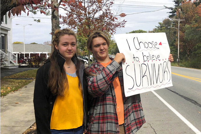 In this Monday, Oct. 7, 2019 photo provided by Shael Norris, high school sophomore Aela Mansmann, 15, of Cape Elizabeth, Maine, left, stands with her brother Aidan, 13, as he displays a placard during a school walkout, in Cape Elizabeth. The American Civil Liberties Union of Maine is calling on a federal court to stop the suspension of Aela Mansmann who accused an unnamed person of sexual assault. Aela and Aidan participated in the school walkout meant to protest the suspension of Aela and two other students. (Shael Norris via AP)