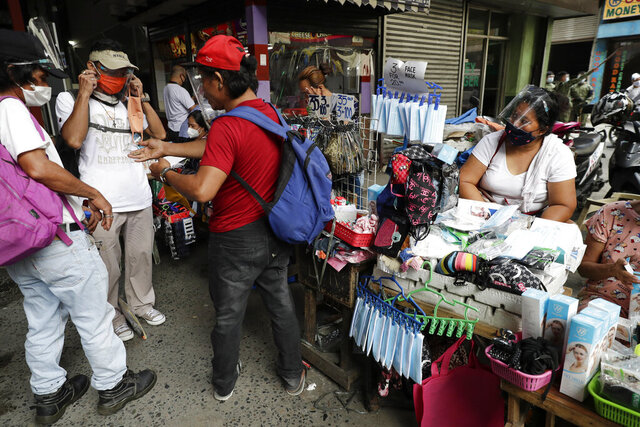 Men buy face masks to help curb the spread of the COVID-19 in Caloocan city, Philippines on Wednesday, Aug. 19, 2020. Philippine President Rodrigo Duterte has decided to ease a mild coronavirus lockdown in the capital and four outlying provinces to further reopen the country's battered economy despite having the most reported infections in Southeast Asia. (AP Photo/Aaron Favila)
