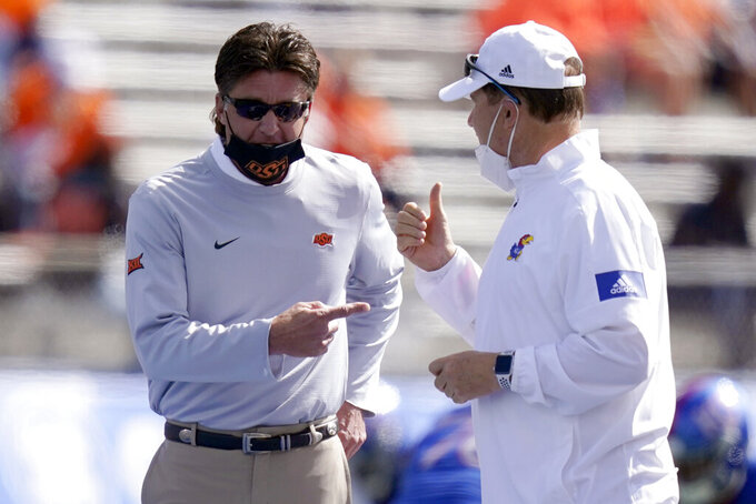 Oklahoma State head coach Mike Gundy, left, and Kansas head coach Les Miles talk before an NCAA college football game in Lawrence, Kan., Saturday, Oct. 3, 2020. (AP Photo/Orlin Wagner)