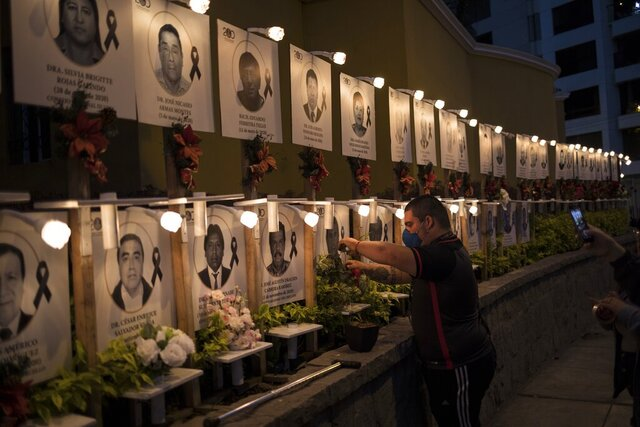 Javier Casana leaves flowers on the portrait of his uncle Jorge Luis Casana, 62, a doctor who died from COVID-19, in Lima, Peru, Tuesday, January 19, 2021. The Peruvian Medical College reported that at least 11 doctors have died during the first days of 2021. (AP Photo/Rodrigo Abd)