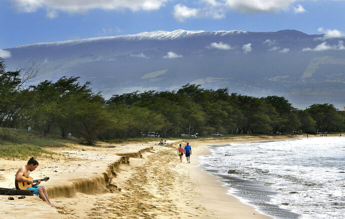 In this Monday, Feb. 11, 2019 photo, with snow-capped Haleakala serving as a backdrop, Paia Maui's Scott Picton, left, plays a guitar and Saskatchewan's Shannon and Dan Runcie walk on Sugar Beach in South Maui, Hawaii. The summit area of Haleakala National Park is closed because of