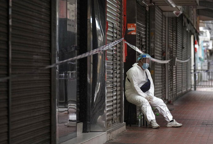 A government worker wearing personal protective equipment guards at the closed area in Jordan district, in Hong Kong, Sunday, Jan. 24, 2021. Thousands of Hong Kong residents were locked down Saturday in an unprecedented move to contain a worsening outbreak in the city, authorities said. (AP Photo/Vincent Yu)