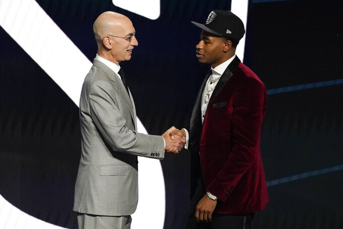 Cameron Thomas, right, greets NBA Commissioner Adam Silver after being selected 27th overall by the Brooklyn Nets during the NBA basketball draft, Thursday, July 29, 2021, in New York. (AP Photo/Corey Sipkin)