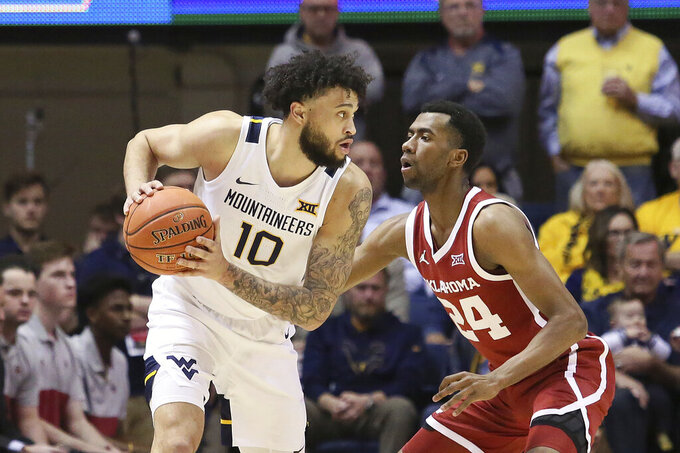 West Virginia guard Jermaine Haley (10) looks to pass the ball while defended by Oklahoma guard Jamal Bieniemy (24) during the first half of an NCAA college basketball game Saturday, Feb. 29, 2020, in Morgantown, W.Va. (AP Photo/Kathleen Batten)
