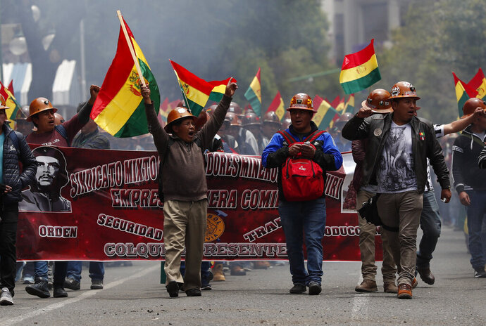 Miners show their support for Bolivian President Evo Morales during a march in La Paz, Bolivia, Monday, Oct. 28, 2019. Bolivian officials say they're negotiating with the Organization of American States for an audit of the country's presidential election, which is being challenged by opponents who say it fraudulently gave Morales an outright re-election victory. (AP Photo/Juan Karita)