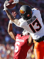 Oklahoma State wide receiver Tyron Johnson (13) makes a catch for a touchdown over Oklahoma cornerback Tre Brown (6) in the first half of an NCAA college football game in Norman, Okla., Saturday, Nov. 10, 2018. (AP Photo/Alonzo Adams)