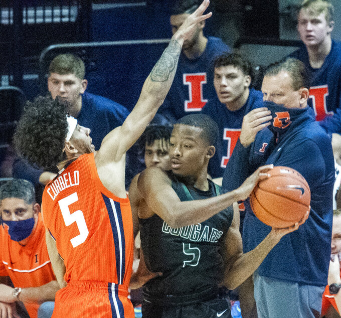 Illinois guard Andre Curbelo (5) defends as Chicago State's guard Xavier Johnson (5) looks to pass while Illinois head coach Brad Underwood, right, watches during the first half of an NCAA college basketball game in Champaign, Ill., Thursday, Nov. 26, 2020. (Robin Scholz/The News-Gazette via AP)
