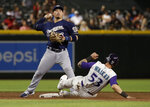Milwaukee Brewers' Keston Hiura forces out Arizona Diamondbacks' Christian Walker (53) as he turns a double play on Adam Jones during the sixth inning of a baseball game Thursday, July 18, 2019, in Phoenix. (AP Photo/Matt York)