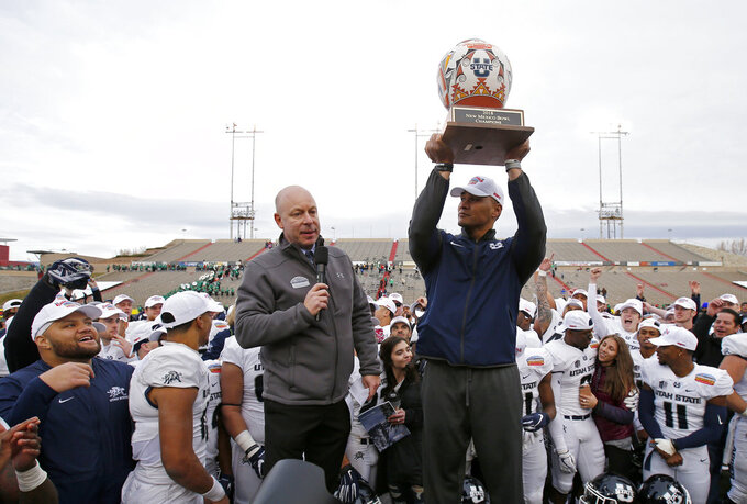 Utah State interim head coach Frank Maile lifts the trophy after his team's 52-13 victory over North Texas in the New Mexico Bowl NCAA college football game in Albuquerque, N.M., Saturday, Dec. 15, 2018. (AP Photo/Andres Leighton)