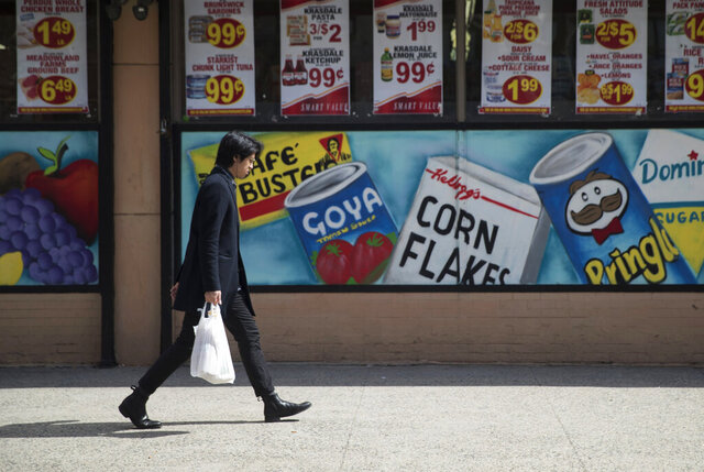 In this March 27, 2019 file photo, a man leaves a supermarket in the East Village neighborhood of Manhattan carrying his groceries in a plastic bag. New York retailers have begun giving up single-use plastic bags as the state prepares for the March 1, 2020, implementation of a ban aimed at reducing pollution. But some worry the state's new regulations include a loophole that could potentially allow stores to phase in plastic bags thick enough to be considered multiuse. (AP Photo/Mary Altaffer, File)