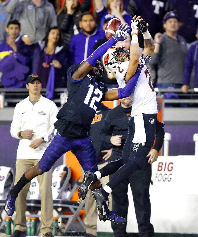 TCU cornerback Jeff Gladney (12) keeps Oklahoma State wide receiver Tylan Wallace (2) from catching a second-half pass during an NCAA college football game Saturday, Nov. 24, 2018, in Fort Worth, Texas. TCU won 31-24. (Tom Fox/The Dallas Morning News via AP)